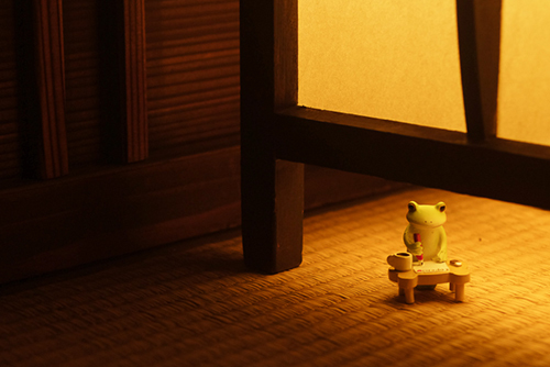 ツバキアキラが撮ったカエルのフィギュア。行灯の灯りのもとで、静かに手紙を書いているコポタロウ。