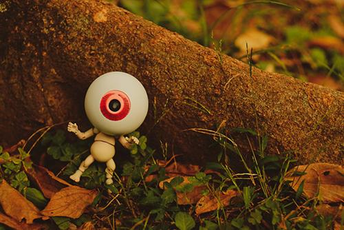 ツバキアキラが撮った、海洋堂・タケヤ式自在置物・目玉おやじ。木の根っこにもたれて、何かあたふたとしている、目玉おやじ。