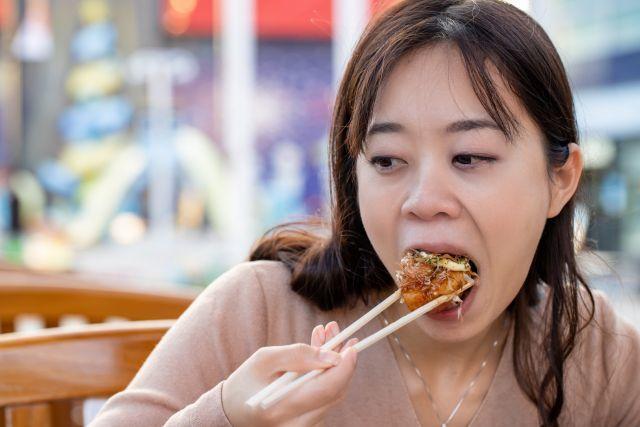 割りばしを折って タコ焼きを食べる女性