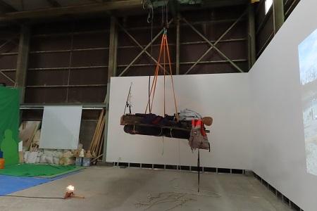 作品は籠に載せられ大型のフックで釣り上げている